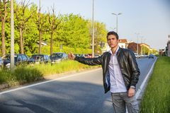 Handsome young man, hitchhiker waiting on roadside Royalty Free Stock Photography