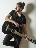 Handsome young man holding acoustic guitar Stock Photography