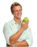 Handsome young man holding an apple Stock Photography