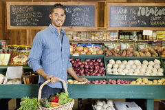 Handsome young man holding basket at vegetable stall in supermarket Stock Photos