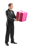 Handsome young man holding a big present Stock Images