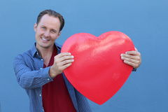 Handsome young man holding big red heart symbol on blue background Royalty Free Stock Photography