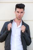 Handsome young man holding black leather jacket Stock Photography