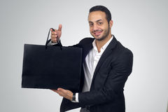 Handsome young man holding a black shopping bag Royalty Free Stock Photos