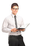 Handsome young man holding a book Royalty Free Stock Image
