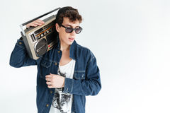 Handsome young man holding boombox. Image of handsome young man wearing glasses standing over white background and holding boombox. Looking aside royalty free stock photo