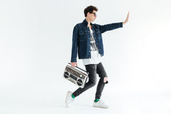 Handsome young man holding boombox. Looking aside. Picture of handsome young man wearing glasses posing isolated over white background and holding boombox Royalty Free Stock Image