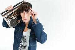 Handsome young man holding boombox. Looking at camera. Image of handsome young man wearing sunglasses standing isolated over white background and holding Royalty Free Stock Images