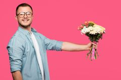 handsome young man holding bouquet of flowers and smiling at camera isolated