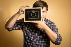 Handsome young man holding camera drawn on small blackboard Royalty Free Stock Image