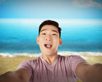 Handsome young man holding camera and making selfie on the beach Stock Image