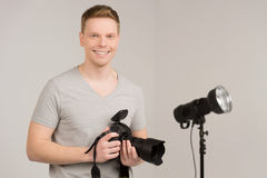 Handsome young man holding camera. Royalty Free Stock Photo