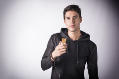 Handsome young man holding the cereal bar he's eating Royalty Free Stock Images
