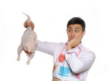 Handsome young man holding chicken ready to cook Stock Photos