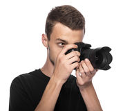 Handsome young man holding a DSLR camera. On white Stock Images