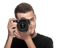Handsome young man holding a DSLR camera. On white Royalty Free Stock Photo