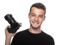 Handsome young man holding a DSLR camera. On white Royalty Free Stock Photography