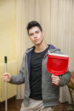 Handsome Young Man Holding Dust Pan and a Broom. Young Handsome Man in Casual Outfit Holding Red Dust Pan and the Stick of a Broom, Looking at the Camera Stock Images