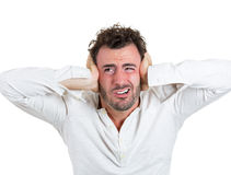 Handsome young man holding ears to avoid loud annoying noise. Closeup portrait of a young handsome beard man in white shirt holding hands to ears covering to royalty free stock photo