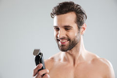 Handsome young man holding electric razor stock images