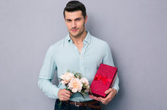 Handsome young man holding gift box and flowers. Over gray background. Looking at camera Stock Photo