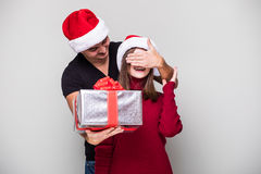 Handsome young man holding a gift box while her girlfriend standing behind him and covering his eyes Royalty Free Stock Photos