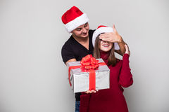 Handsome young man holding a gift box while her girlfriend standing behind him and covering his eyes Stock Image