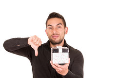 Handsome young man holding a gift box. With thumb down isolated on white Royalty Free Stock Photography