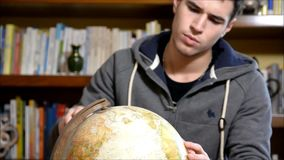Handsome young man holding a globe indoors at home looking at the camera stock video