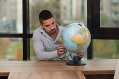 Handsome Young Man Holding A Globe At Office Royalty Free Stock Images