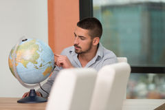 Handsome Young Man Holding A Globe At Office Royalty Free Stock Image