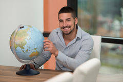 Handsome Young Man Holding A Globe At Office Stock Image