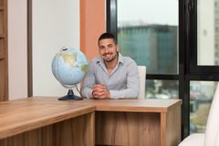 Handsome Young Man Holding A Globe At Office Stock Photography