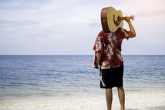 Handsome young man holding guitar over shoulder on the beach with the blue sky Royalty Free Stock Images