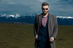 Handsome young man holding his hand in his pocket. And confidently looking forward while wearing a gray coat, blue suit and sunglasses, standing on outdoor stock photo