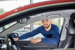Attractive driver in blue sweater leaning on red vehicle. Handsome young man holding his hands on car`s front door from passengers side. Attractive brunette stock photography