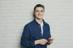 Handsome young man holding mobile phone and looking at it while standing against brick wall Stock Images