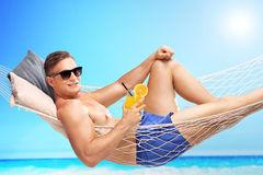 Handsome young man holding an orange cocktail. And lying in a hammock at a sunny beach by an ocean Royalty Free Stock Images