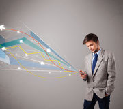 Handsome young man holding a phone with colorful abstract arrows Royalty Free Stock Image
