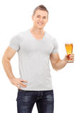 Handsome young man holding a pint of beer. Isolated on white background royalty free stock image