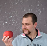 Handsome young man is holding a red  apple standing Stock Photos