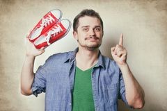 Handsome young man holding red gumshoes Royalty Free Stock Photography
