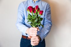 Handsome young man holding red rose bouquet, romantic Valentines day surprise, love,flowers royalty free stock photography