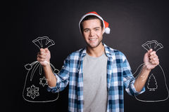 Handsome young man holding sacks of Christmas gifts. Stock Images