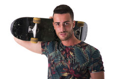 Handsome young man holding skateboard on his shoulder Stock Photo