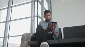 Handsome Young Man Holding Tablet PC And Working at The Airport, Technology, Travelling Concept stock image
