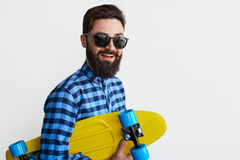Handsome young man holding yellow skateboard Royalty Free Stock Photo