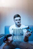 Handsome young man holing two consoles sitting on the sofa at ho Royalty Free Stock Image