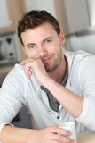 Handsome young man at home kitchen drinking coffee Royalty Free Stock Images