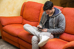 Handsome young man at home reading with ebook Royalty Free Stock Photo